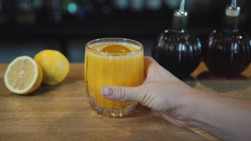 An alcoholic cocktail is put on the bar. A hand is putting a glass with a yellow cocktail and ice on the table. Food video. Video for restaurants and cafes.