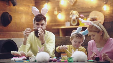 Mother, father and son are painting easter eggs. Happy family are preparing for Easter. Cute little child boy wearing bunny ears. Easter eggs on wooden background. Happy easter