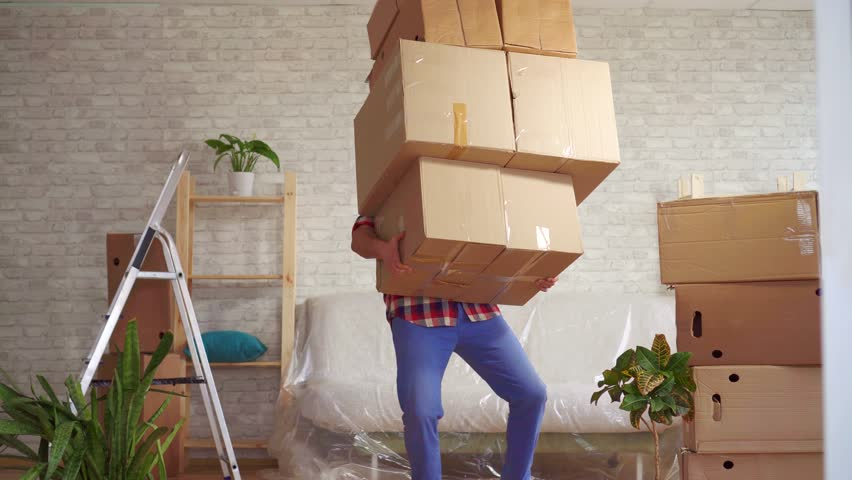 Man with large boxes in his hands falls on the sofa | Shutterstock HD Video #1026672125