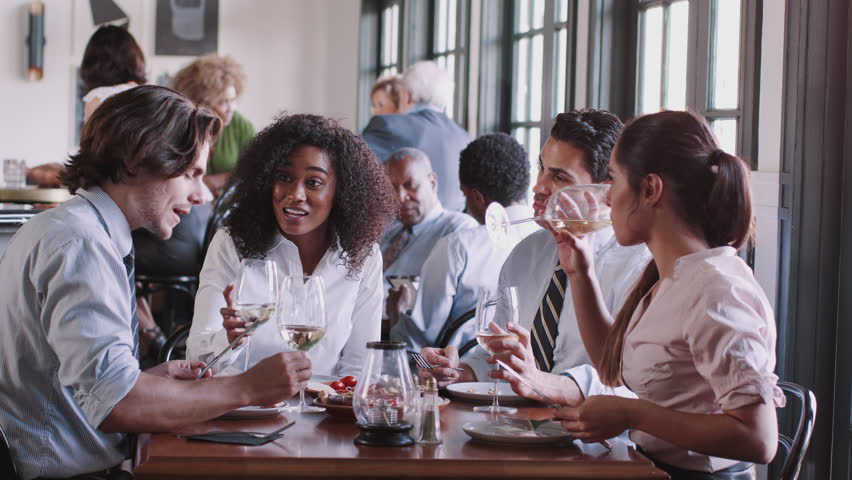 Business Colleagues Sitting Around Restaurant Table Enjoying Meal Together   Shutterstock HD Video #1026690455