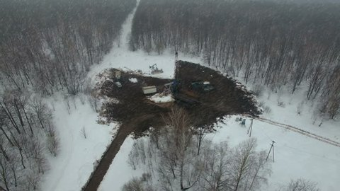 Drilling a deep well with a drilling rig in an oil and gas field in winter forest. The field is located in Kamchatka, Tundra, Yamal, North, West, Siberia, fog, aerial, snowfall, flakes, snowstorm