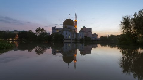 Time Lapse of a clear sunrise view at Royal City Mosque by a river with reflection in Klang, Selangor, Malaysia. Twilight to Day. Zoom out motion timelapse.