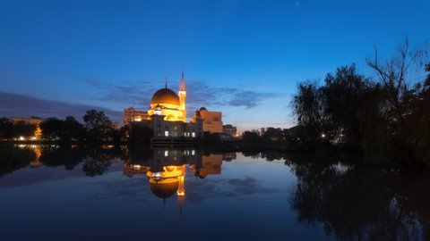 Time Lapse of a clear sunrise view at a mosque by a river with reflection in Selangor, Malaysia. Twilight to Day.