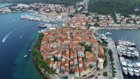 4K aerial panorama of coast of Croatian city Korcula made in the morning during sunrise. Old city with tower, marina and big luxury yachts are visible