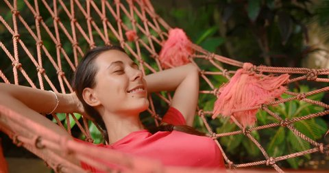 Attractive young woman rejoices life lying in a hammock. The girl smiles and looks very happy and successful. tracking shot. in slow motion