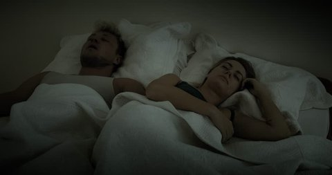 Woman buries her head under her pillow to get away from her partners loud snoring
