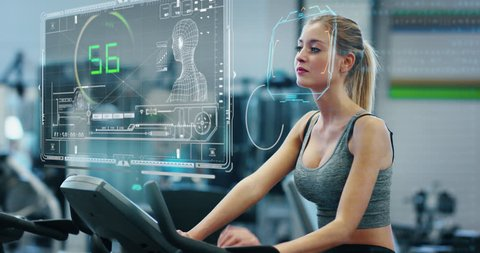 Portrait of an young beautiful girl in the gym on a stationary bike using augmented reality futuristic hologram to strengthen her body measuring heartbeat and pressure.