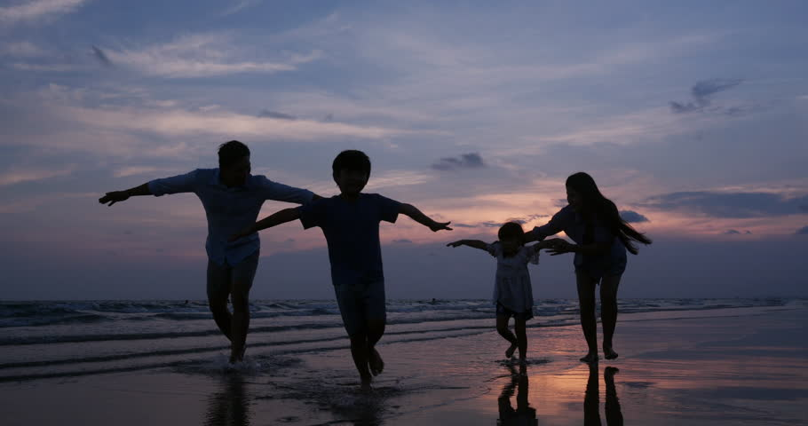 SLOW MOTION, Silhouetted Asian family running together at Beach. Family, Freedom and Travel concept. #1026856235