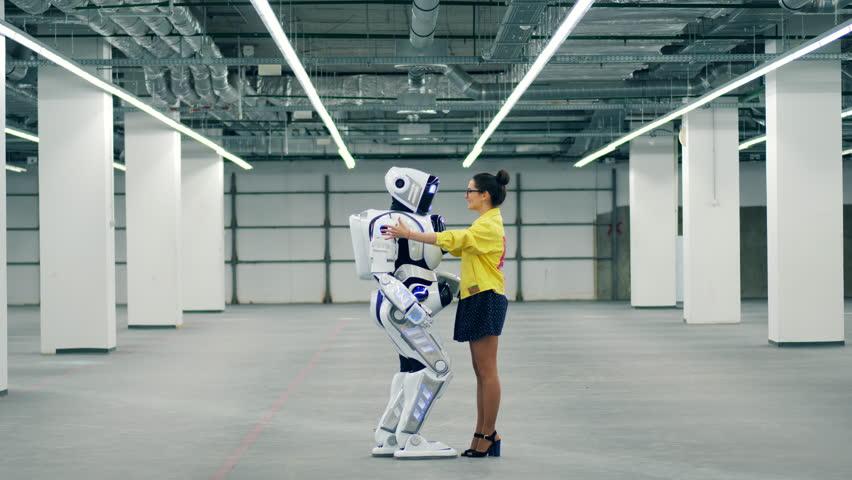 Woman greets her robot friend, hugging it. | Shutterstock HD Video #1026880475