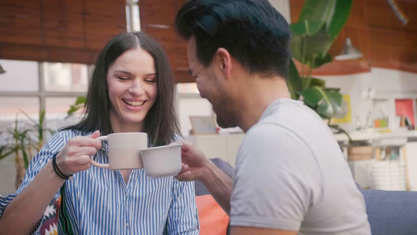 Portrait of cute young couple enjoying tasty house made drink, spending leisure time together, smiling and kissing each other, chilling on comfortable couch, dressed in basic clothes | Shutterstock HD Video #1026888845