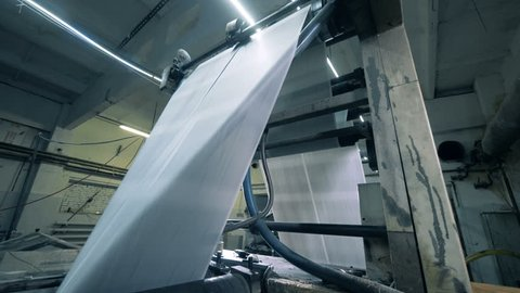 Paper rolling on a conveyor in a printing office, modern technology.