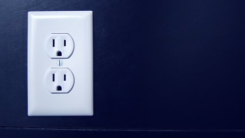 Light turns on and off at night as a cord is plugged into the bottom outlet and red from an American electrical socket, copy space right