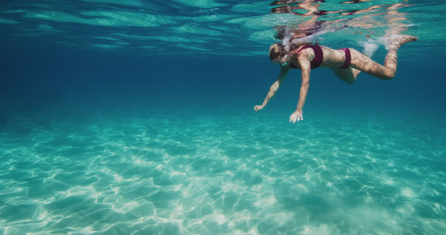 Beautiful young woman swimming and diving in pristine blue ocean water in slow motion, tropical vacation holiday #1027016165