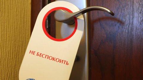 KRASNODAR, RUSSIA - CIRCA 2019: Russian hotel room door sign Do Not Disturb. Red white door hanger swinging on handle.
