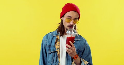 Portrait of the Caucasian young attractive stylish man in a red hat sipping smoothie and looking to the camera on the yellow background.