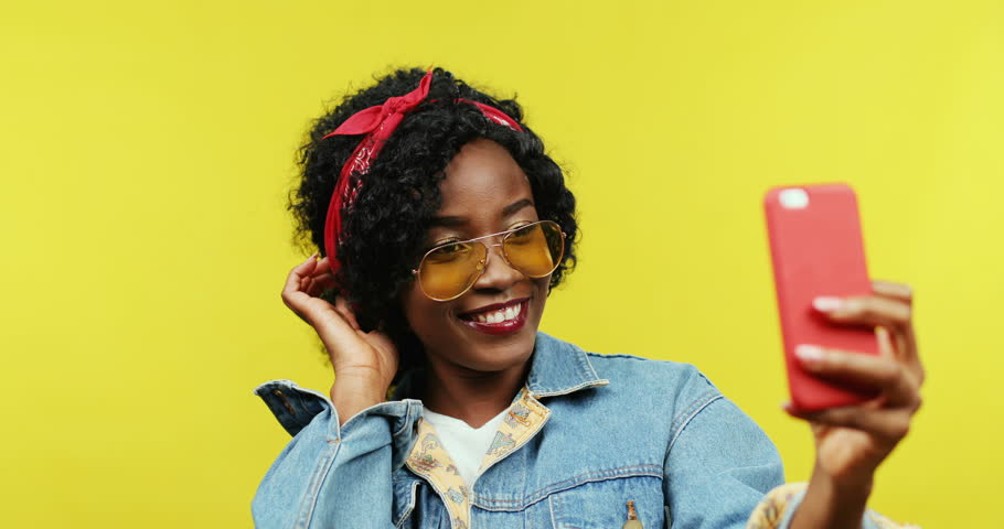 Close up of the young joyful African American woman in sunglasses and stylish look posing to the smartphone camera while taking selfie photos on the yellow background.