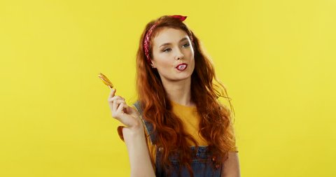 Portrait shot of the cute caucasian stylish young girl with red hair holding a lollipop and chewing a bubble gum on the yellow wall background.