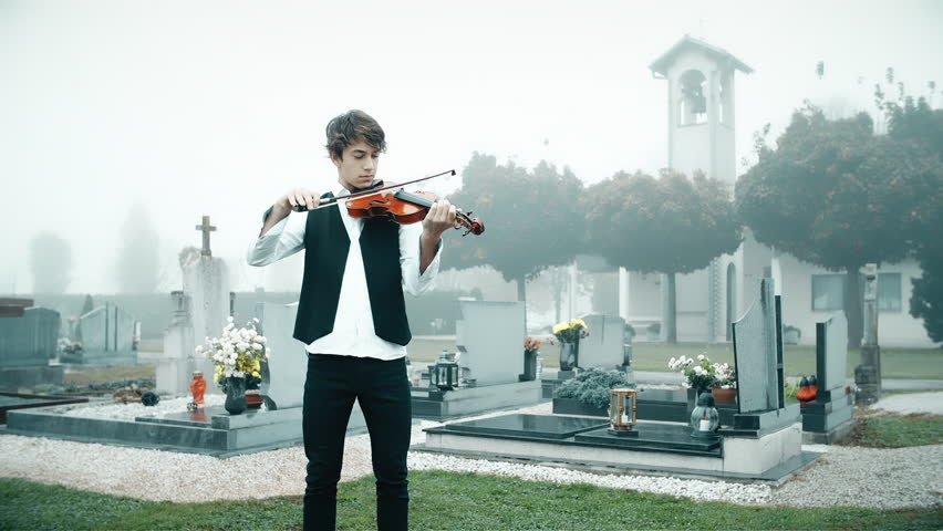 Playing violin on the funeral. Medium long shot of young man in focus with violin on graveyard on a foggy day. | Shutterstock HD Video #1027042955