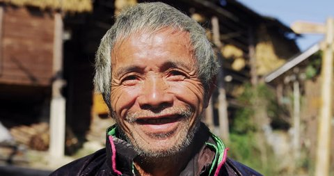Timeless portrait of a real unique authentic Asian Chinese village man, rice farmer of Huanggang mountain village China. Hand held, Red cinema camera, slow motion.