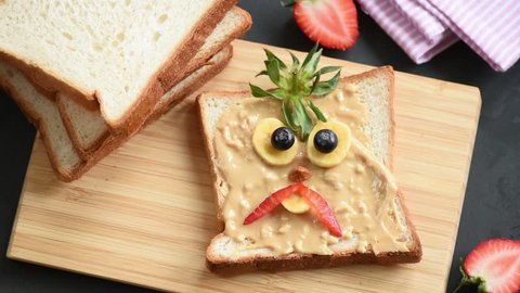 Stop motion animation of making peanut butter toast with funny angry bird face for kids school lunch