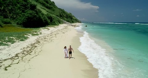 Romantic Couple Holding Hands walking on a white sand empty beach with beautiful blue ocean waves on the side – Lovely young woman and man having honeymoon – 4k Aerial Drone Footage in Bali