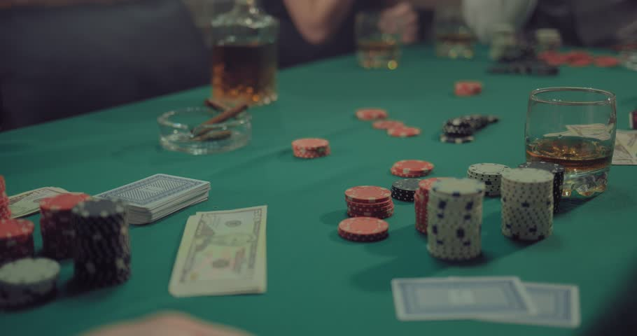 On a green gaming table are chips, money, cards and cigars of players. Company plays poker. Close-up. | Shutterstock HD Video #1027183205