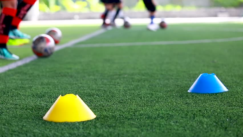 soccer ball on green artificial turf between cones maker with blurry soccer team training, blurry kid soccer player jogging and control ball with soccer equipment in football academy.