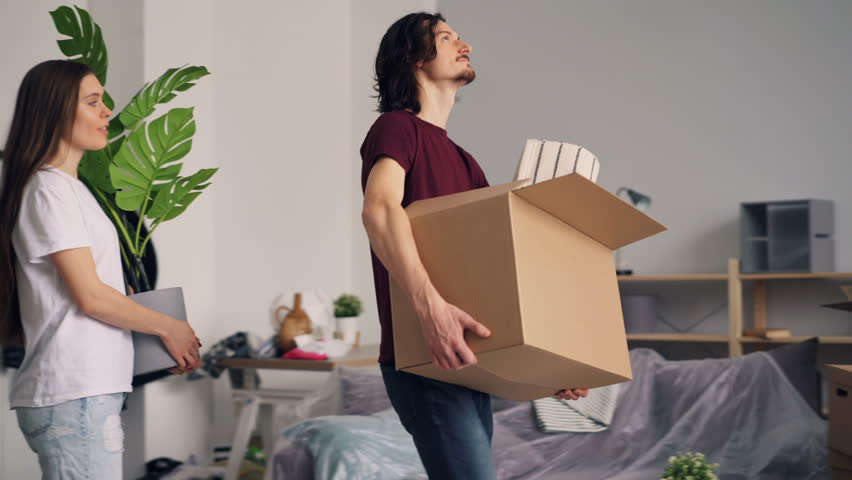 Young man and woman with carton boxes are entering room in new house, looking around with smile and kissing. Relocation, interior and happy family concept.