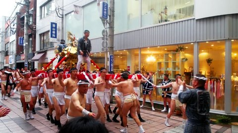 KAGOSHIMA, JAPAN - JULY 22, 2018: Religious festival at the streets of Kagoshima, Japan during the day. Kagoshima is a popular touristic city of Kyushu island. Men shout wearing traditional clothes