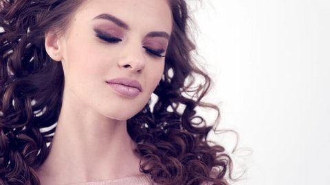 Beautiful woman with long curly hair.  Beauty face. Fashion model. Fashion makeup. Attractive Girl with a smokey eye makeup.  Closeup face of a girl. Slow motion 4k footage. Sexy brunette lady.