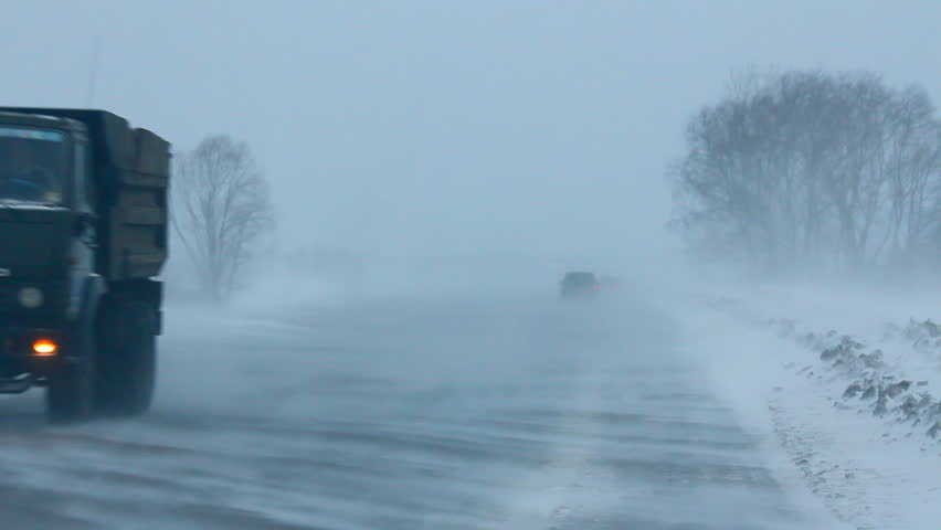 cars on winter road during blizzard