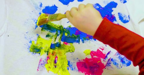 Vivid creative splatter painting by a kid using a brush on a plain white blank t-shirt (close up shot)