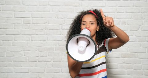 Young people, feelings and emotions. Portrait of happy african american woman shouting with megaphone for promotion, advertising. Black girl smiling and laughing for fun, joy, happiness