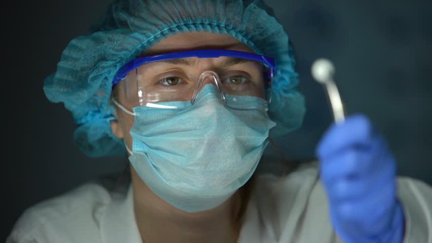 Researcher examining tablet, holding it in forceps, medication development | Shutterstock HD Video #1027292225