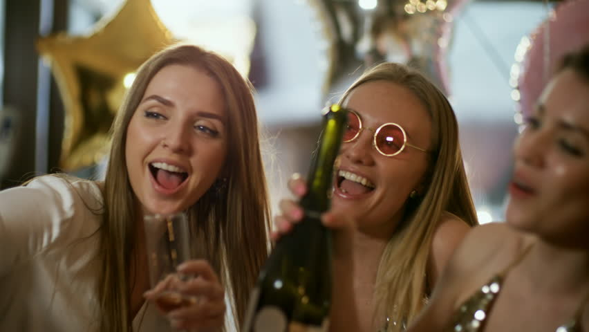 Medium close-up of carefree 20-something ladies having fun at birthday party, smiling, enjoying champagne and taking selfies with smartphone   Shutterstock HD Video #1027314845