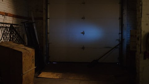 A special ops military SWAT team member walks in dark warehouse past bodies with gun and flashlight walking into a stand off situation. Medium close shot on RED camera.