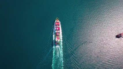 Aerial footage of ultra large container ship at sea, top down view.