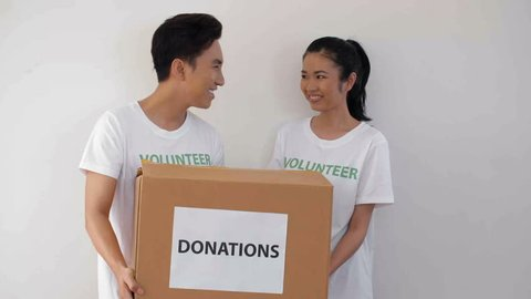 Medium shot of young Asian man and woman standing with donation box in their hands, then coming their female teammate with another donation box. All three standing with donation boxes and smiling