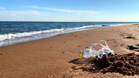 Plastic pollution. A plastic bottle and a six pack plastic rings on the beach shore