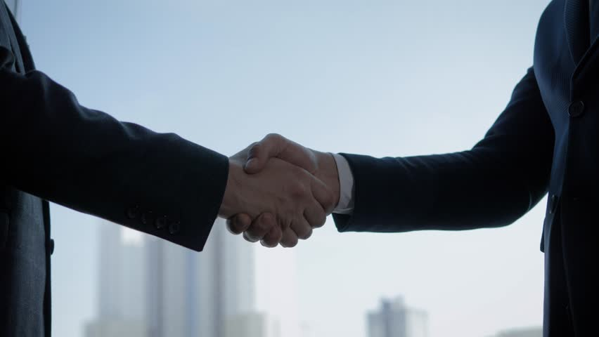 Close up of the hands of top managers in business suits, shake hands with each other, against the window in the office, agree to a deal or say hello. Slow motion, unrecognizable person #1027433285