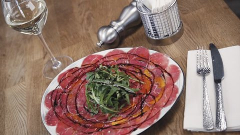 Beef carpaccio with arugula and balsamic acusus. A dish stands on a wooden table in a restaurant. Arrangement with a glass of wine and cutlery.