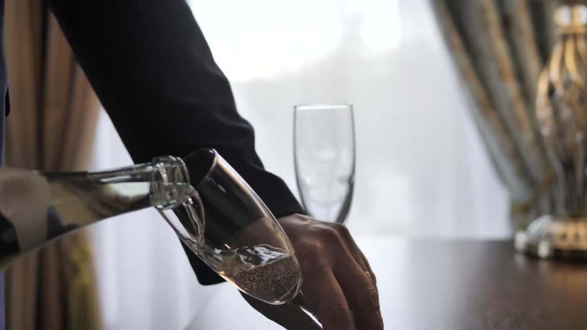 A man's hand in a jacket pours sparkling wine from a bottle into a wine glass. A lampshade lamp stands on the table. Champagne bubbles play in the light next to the second glass cup of slow motion.