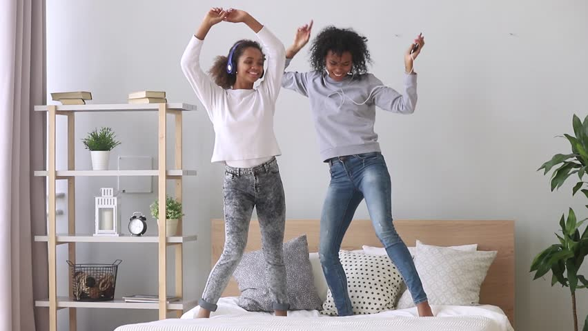 Happy carefree family black mom and teen daughter wearing headphones dancing on bed listening to music on phone, funny funky african american mother sister and teenager girl having fun in bedroom | Shutterstock HD Video #1027488605