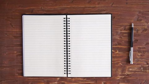 Man's hands turning over clean blank pages from recycled paper in big notebook, isolated on white wooden table , then closing it.