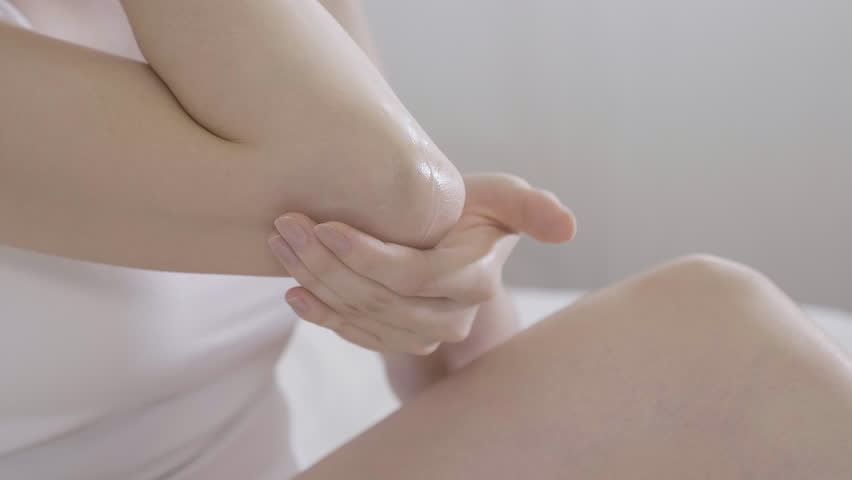 Beauty and body care female elbow pain and health care concept. slow motion of asian woman applying lotion cream moisturizer relaxing in bed in white cozy apartment near window. hand touching careful | Shutterstock HD Video #1027590125