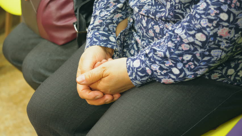 Elderly woman is sitting in line, waiting and keeping her hands joint on her legs. Hands close-up.