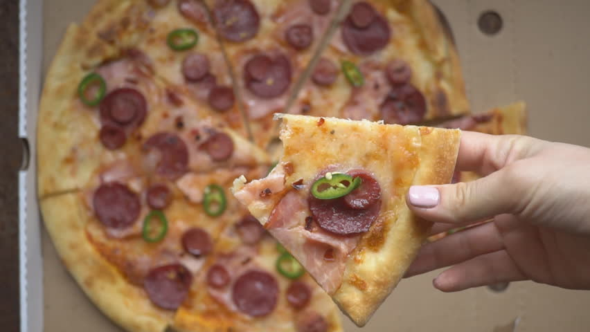 Human hands taking of hot tasty italian pizza from open box, food delivery service at party catering concept, friends having fun enjoying eating hanging out together, close up view | Shutterstock HD Video #1027640285