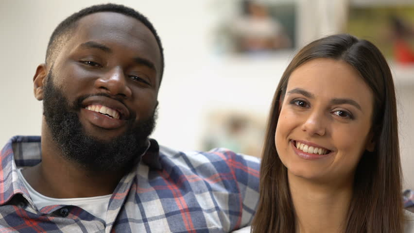 Smiling multi-ethnic couple making heart with hands, symbol of their love | Shutterstock HD Video #1027733585