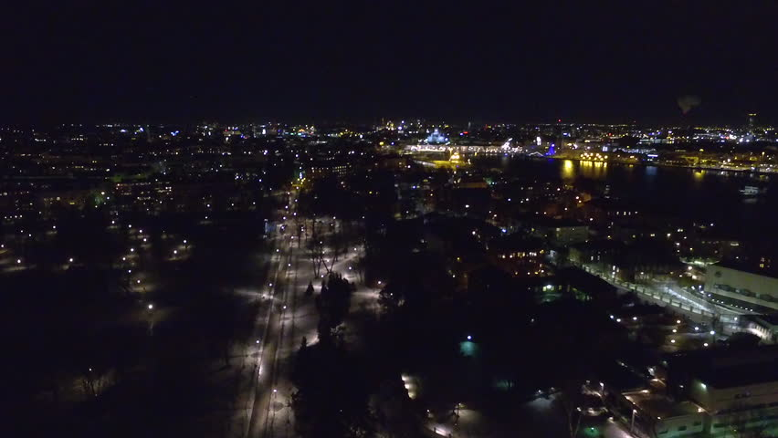 A tracking aerial drone shot, taken at night, that slowly pans downwards to reveal a busy road and intersection bathed in the moody fluorescent glow of street lights. | Shutterstock HD Video #1027740905