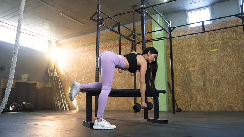 Dolly shot of beautiful strong woman making exercise with dumbbells, leaning on the bench in the  gym full of sunlight. #1027742135